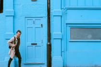 Man walking past a wall and door the same bright light blue colour