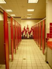 Modern toilet block with red doors on cubicles