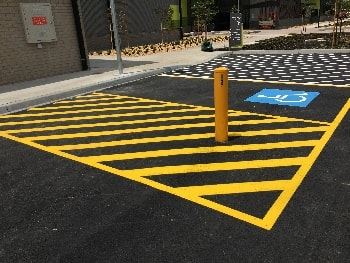 Accessible car parking space with high visibility yellow line marking on black bitumen surface, including a yellow bollard